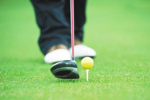 Yellow golf ball teed up for golfer
