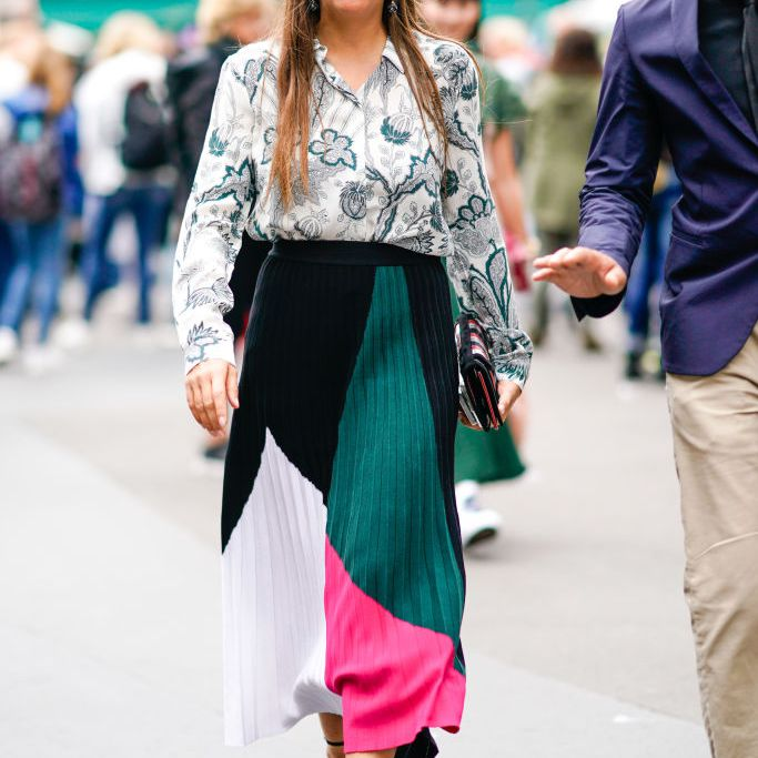 Street style fashion woman in a colorful pleated skirt