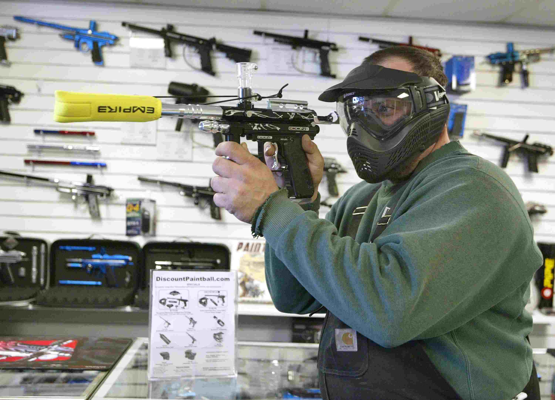 Man examining electronic paintball gun.