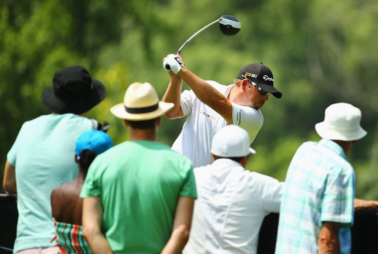 Spectators watch Justin Walters of South Africa as he tees off on the 11th hole on the East Course during day four and the final round of the Joburg Open at Royal Johannesburg and Kensington Golf Club on January 17, 2016
