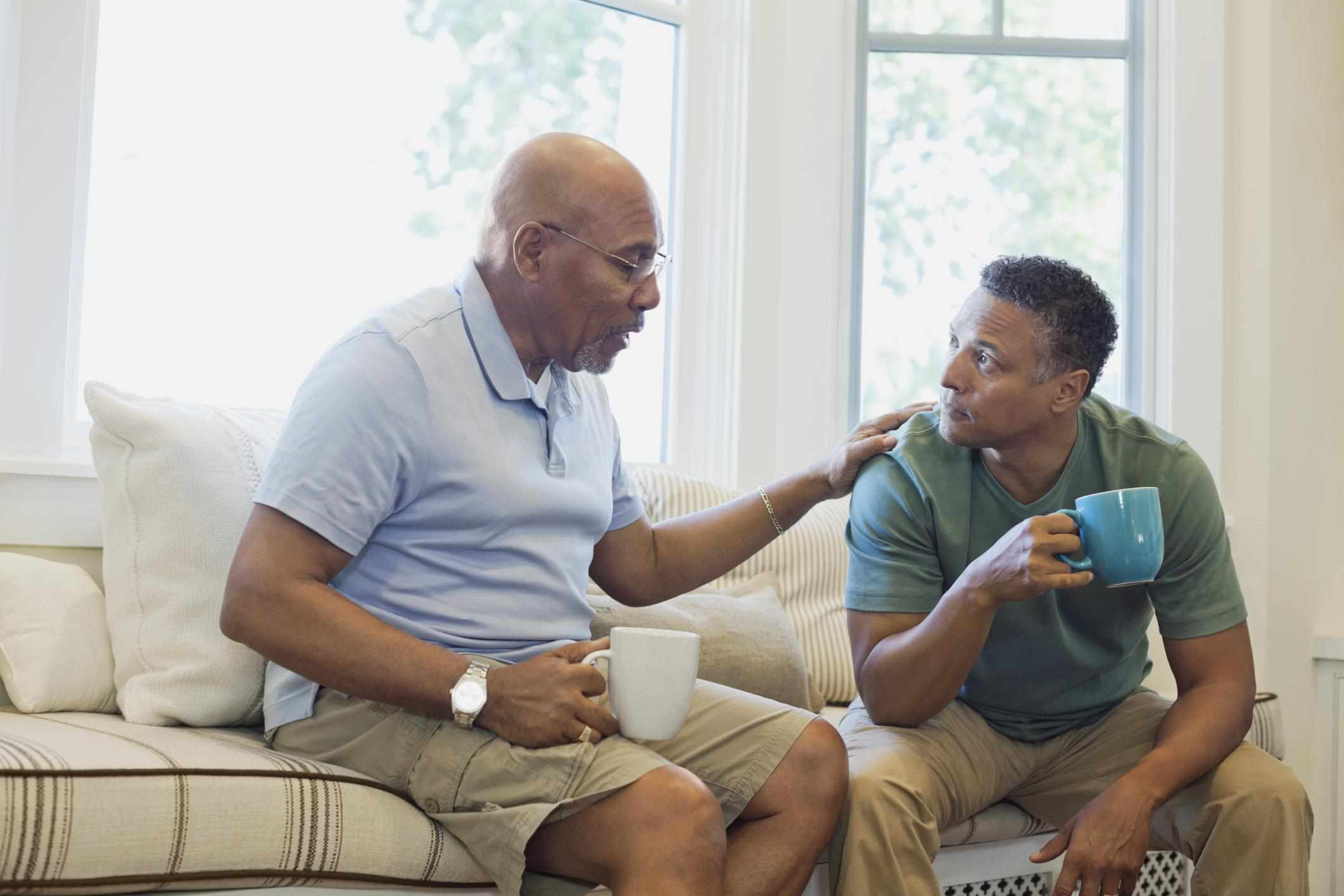 Senior father and adult son talking while having coffee