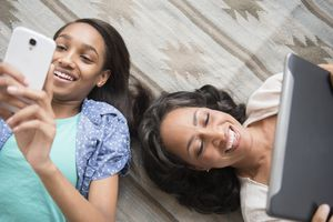 Mother and daughter on the floor texting on personal devices
