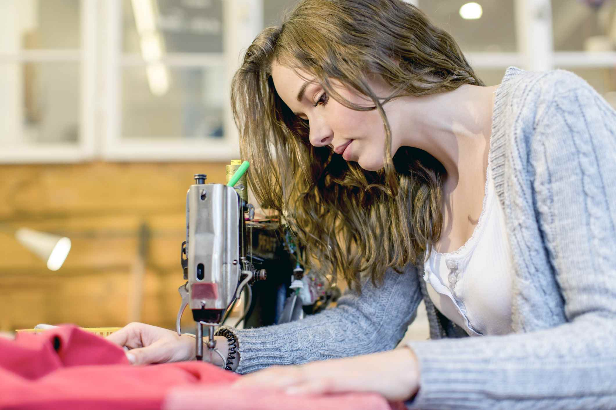 A young seamstress works behind her sewing machine.