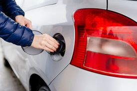 Woman opening fuel filler