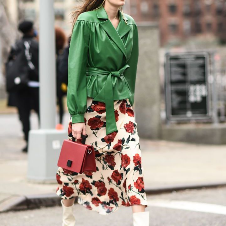 Street style woman in green leather jacket and flower print dress