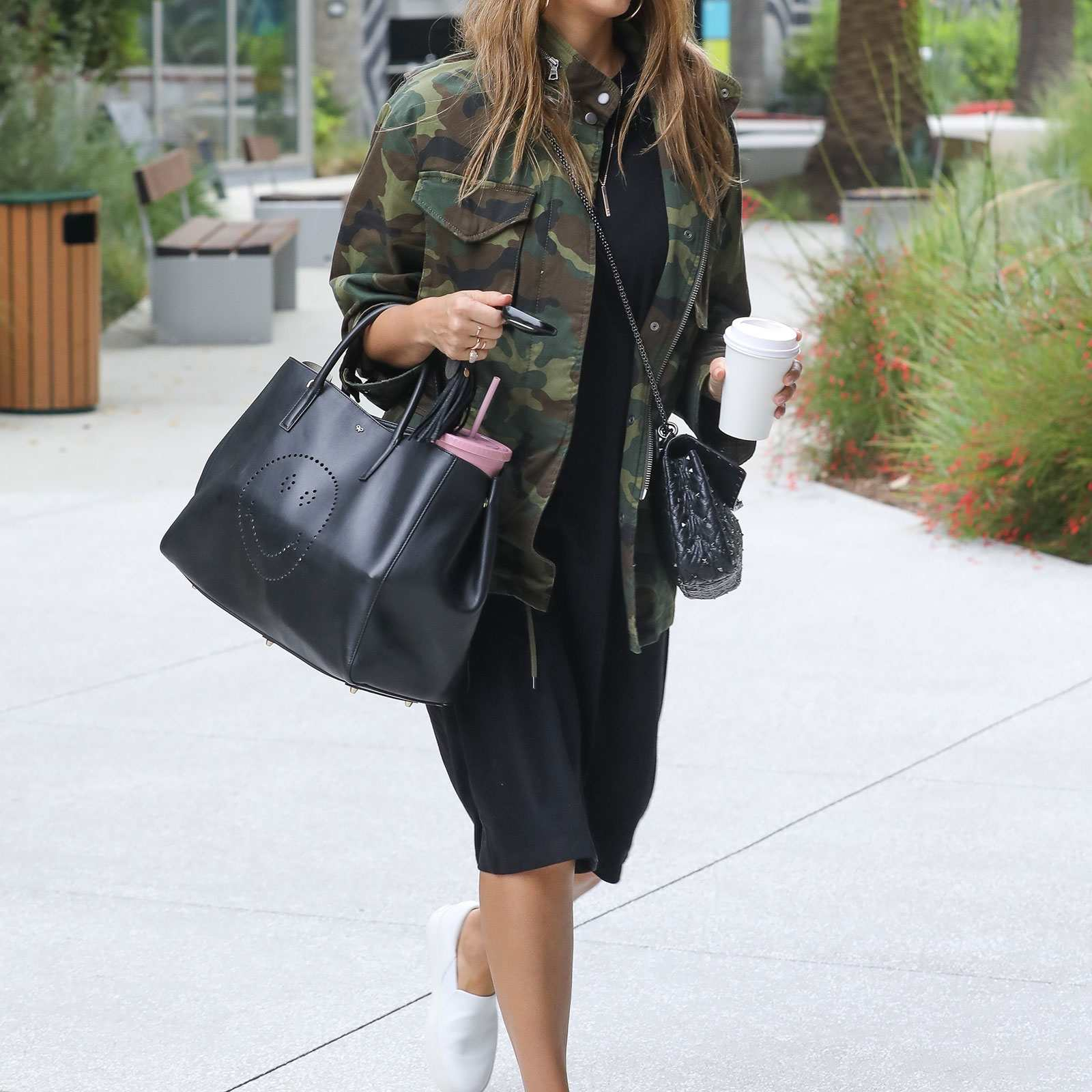 e263c4e18 Woman in camouflage print jacket and black dress and sneakers