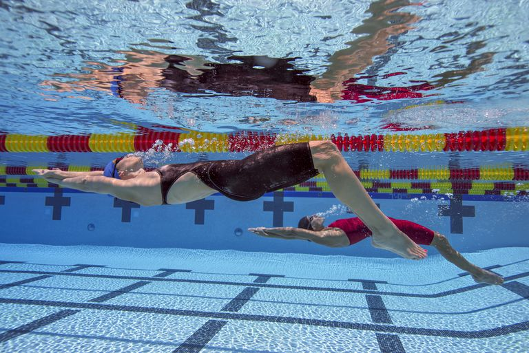 Two women swimming backstroke underwater.