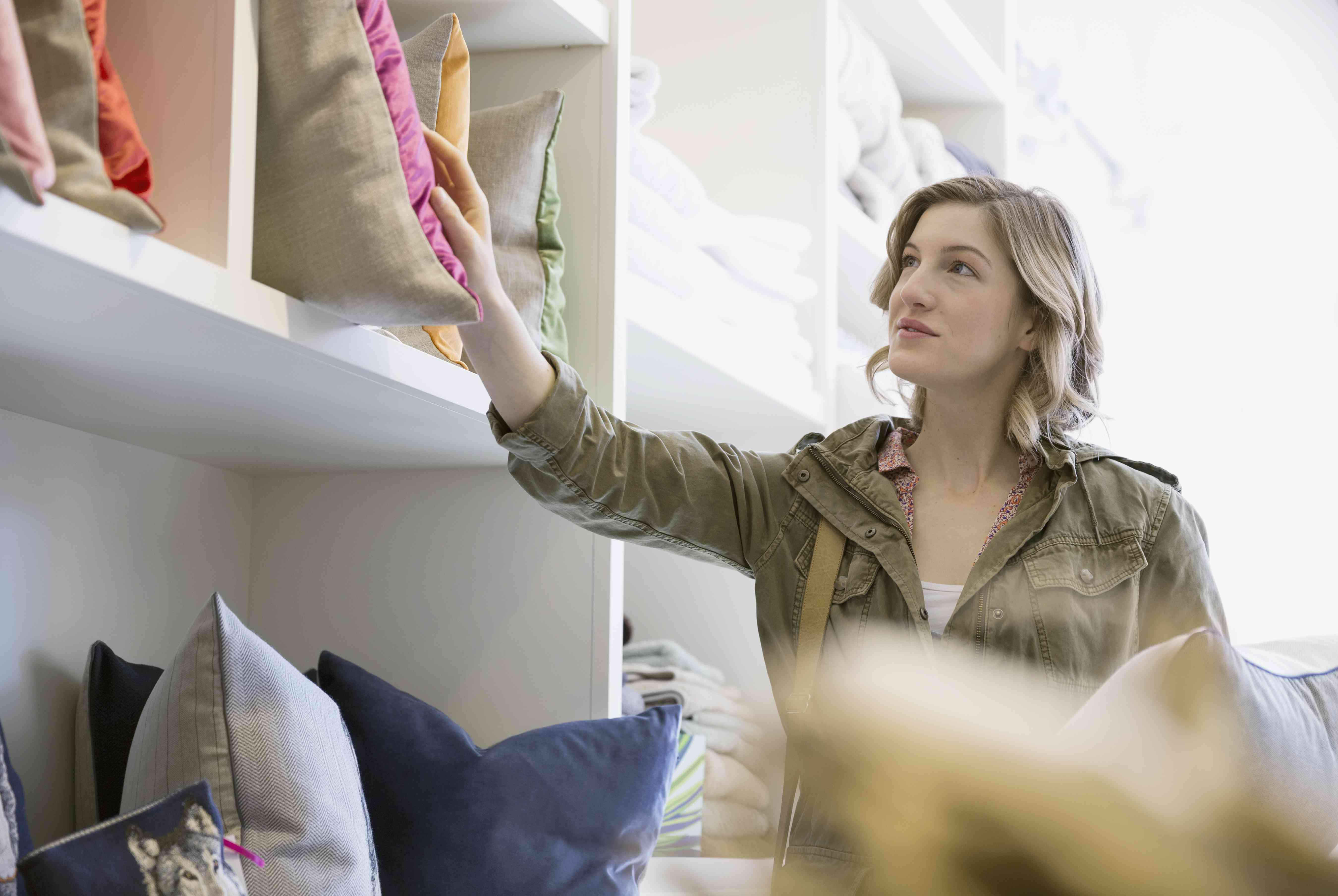Woman looking at pillows in shop