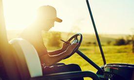 Golfer in a golf cart marking his scorecard.