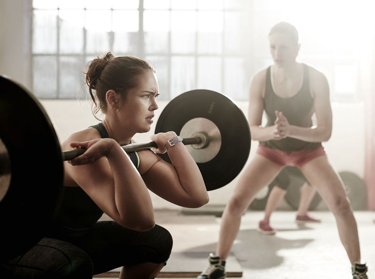 Two women weightlifting in the gym