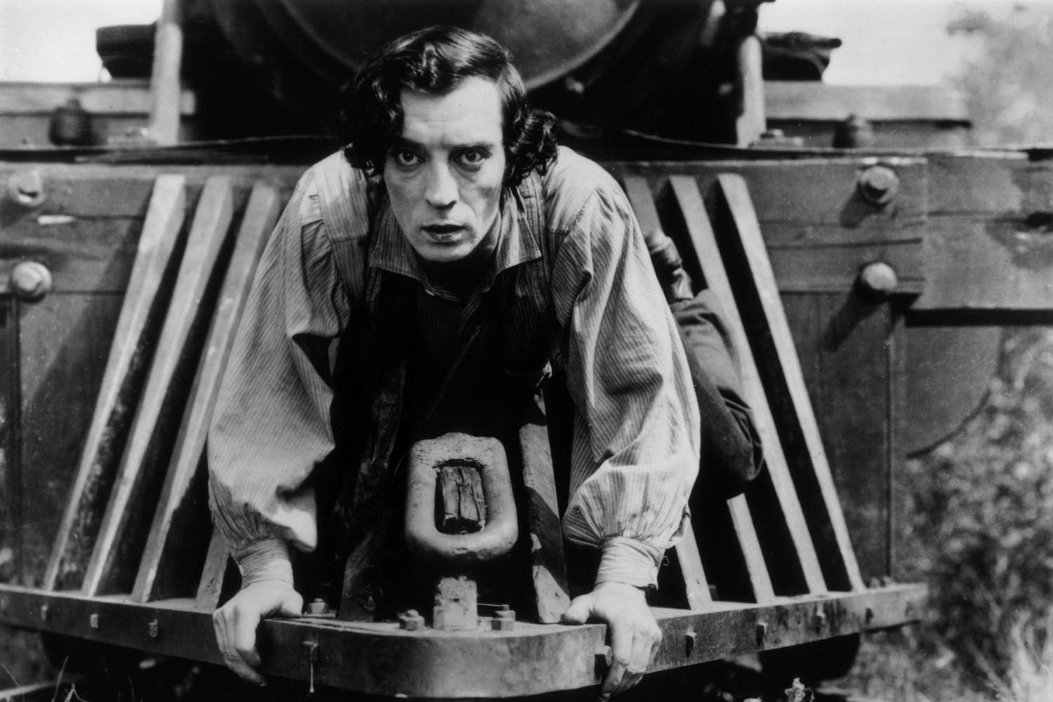 Silent screen comedian Buster Keaton riding the front of a railroad engine in his 1926 film 'The General'