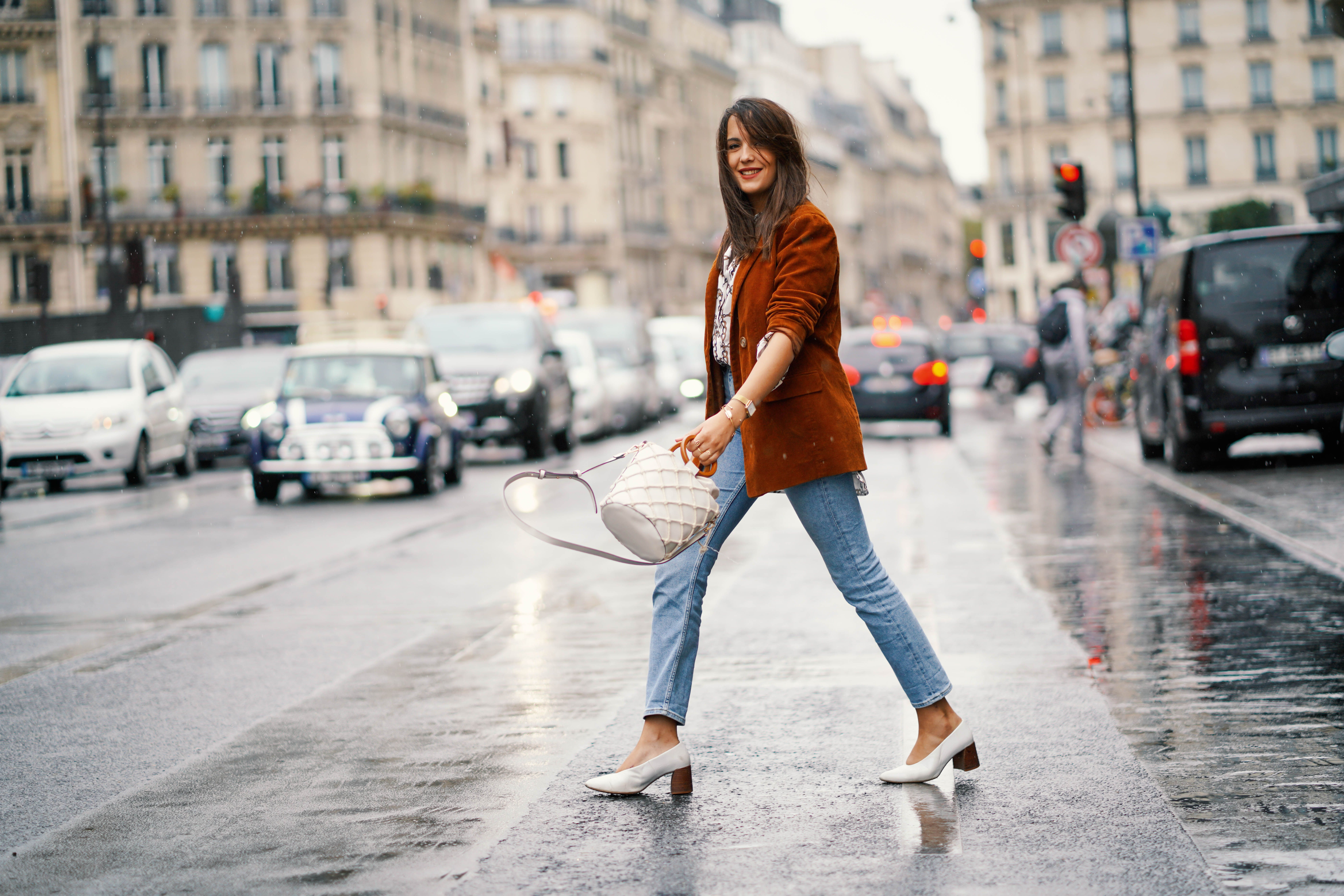 Street style women in jeans and a blazer and white high heel shoess