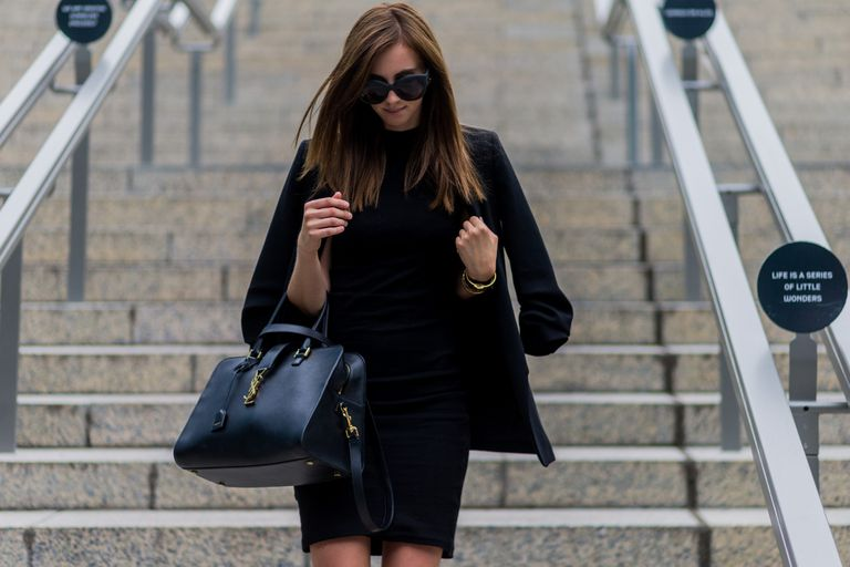 Woman in black blazer and black dress with sunglasses and leather purse