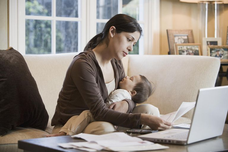 Hispanic woman paying bills online with sleeping baby