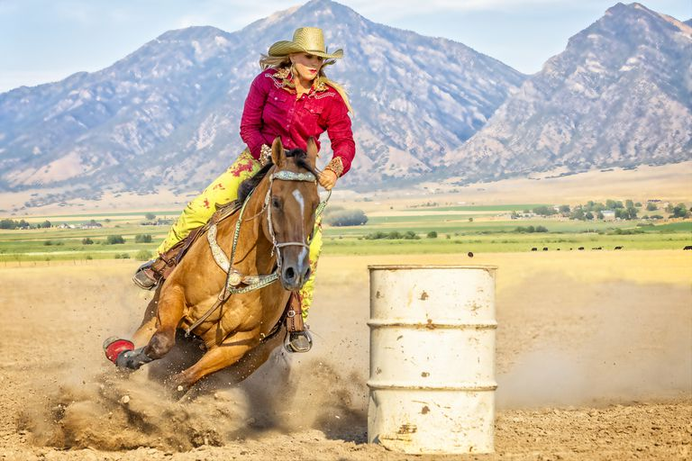 Young Woman heads her horse around a barrel during a barrel racing contest