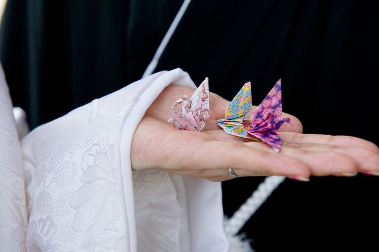 Bride holding three colorful origami cranes.