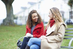 Friends talking on park bench.