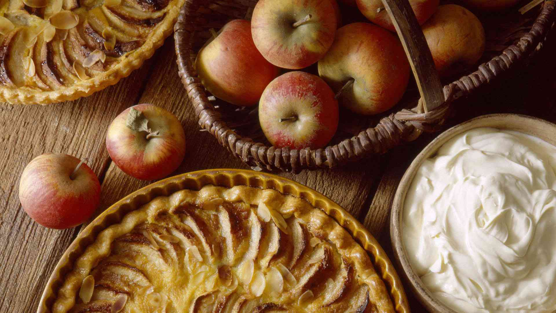 An apple pie and a basket of apples.