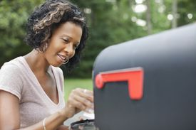 Woman taking checking her mailbox for free samples