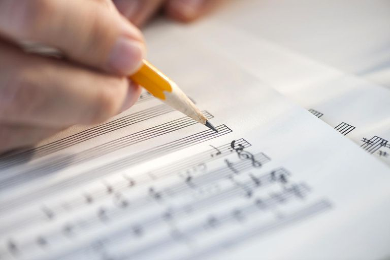 Man writing notes on sheet music