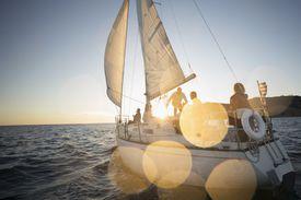 Friends sailing on sunset sailboat