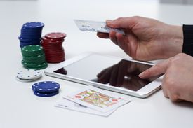 Credit card in hand with casino paraphenalia and a tablet