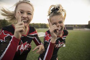 Two enthusiastic teenage girl high school cheerleading team gesturing, celebrating
