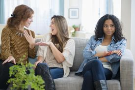 two women ignoring another woman on the same couch