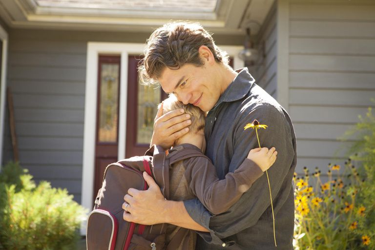 Father Hugging Son With Daisy Before School.