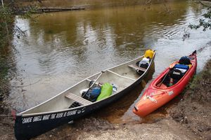A kayak and canoe loaded for a fishing and camping trip.
