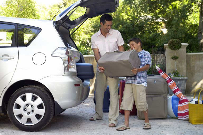 Boy (11-13) helping father load car, struggling with case, smiling