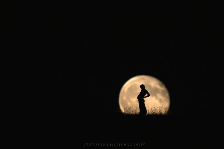 Pregnant woman against a full moon.