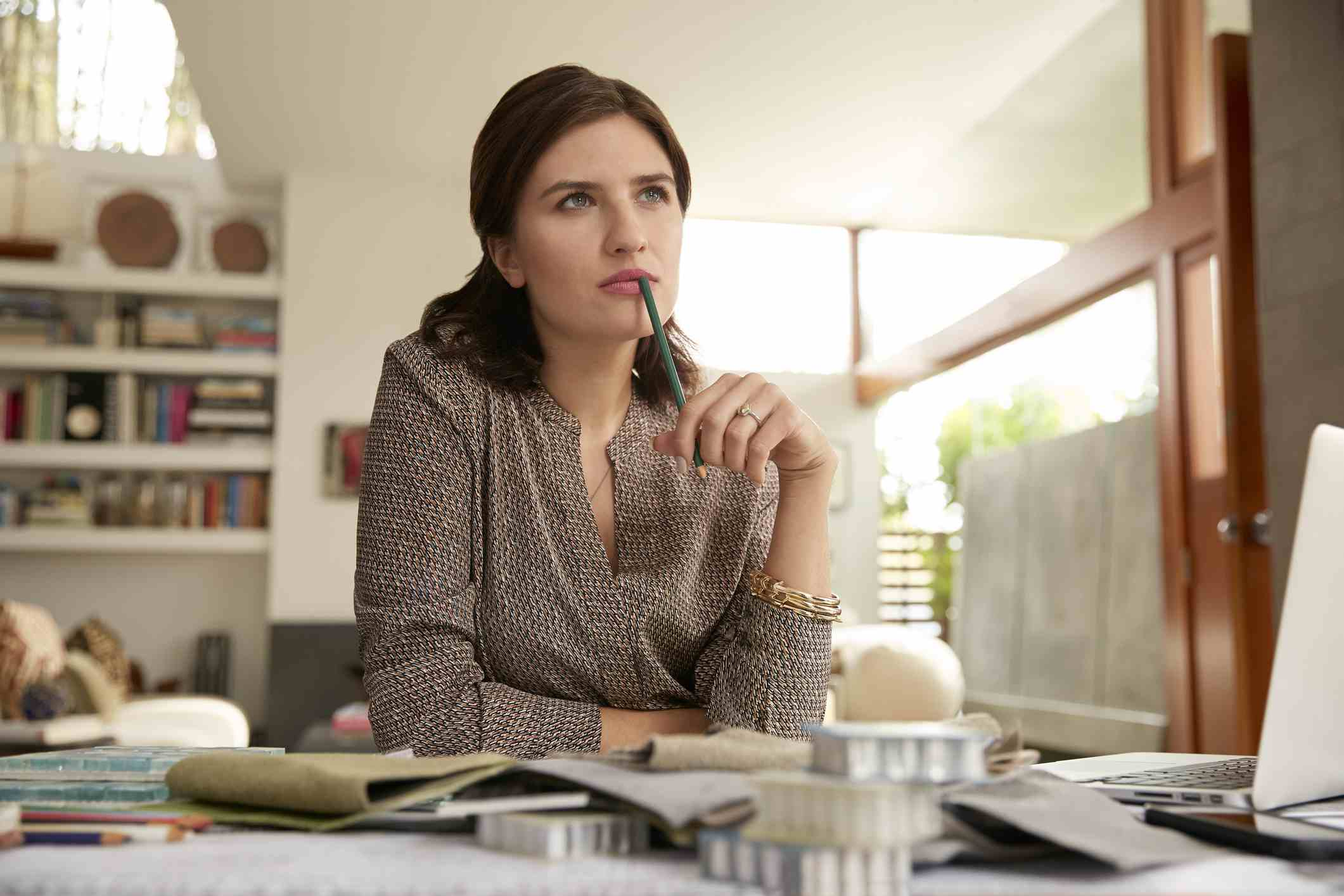 Woman with pencil thinking sitting in front of laptop
