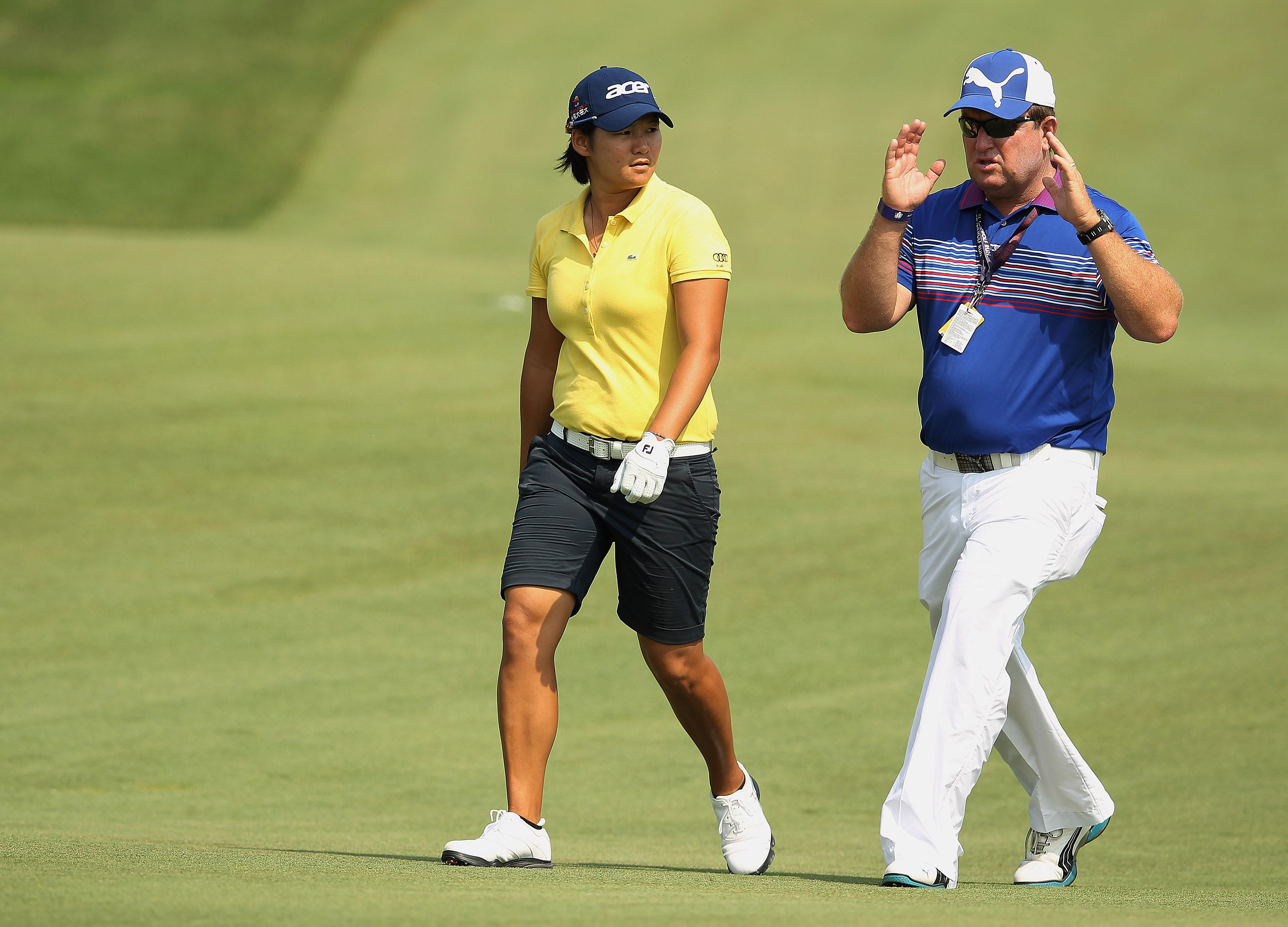 Yani Tseng of Taiwan (L) walks with her coach Gary Gilchrist during a practice round prior to the start of the 2012 U.S. Women's Open