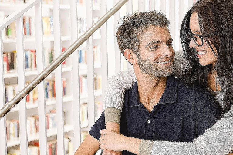 Student couple sitting on staircase of library, smiling