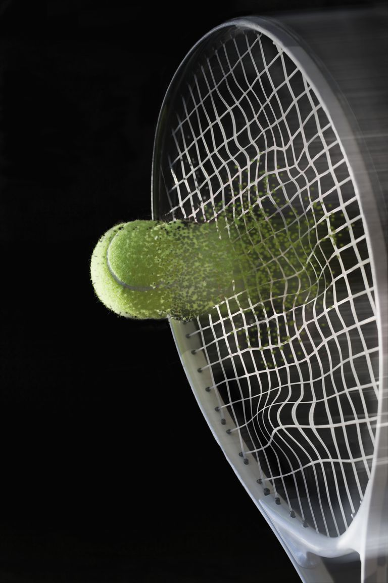 Close up tennis racket hitting ball with blurred motion