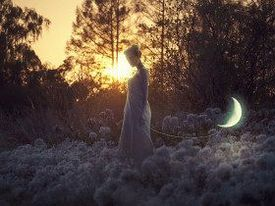 Woman in dark landscape with setting sun and moon