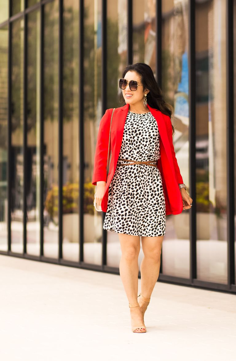 7039c835747c Woman in red blazer and printed black and white dress with belt