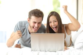 Euphoric marriage winning with a laptop at home