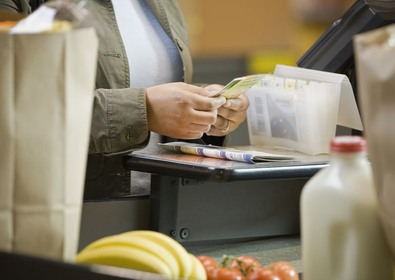 Close up of a person's hands sorting through coupons at a grocery store checkout line. A coupon organizer sits next to the person's hands, near the register.