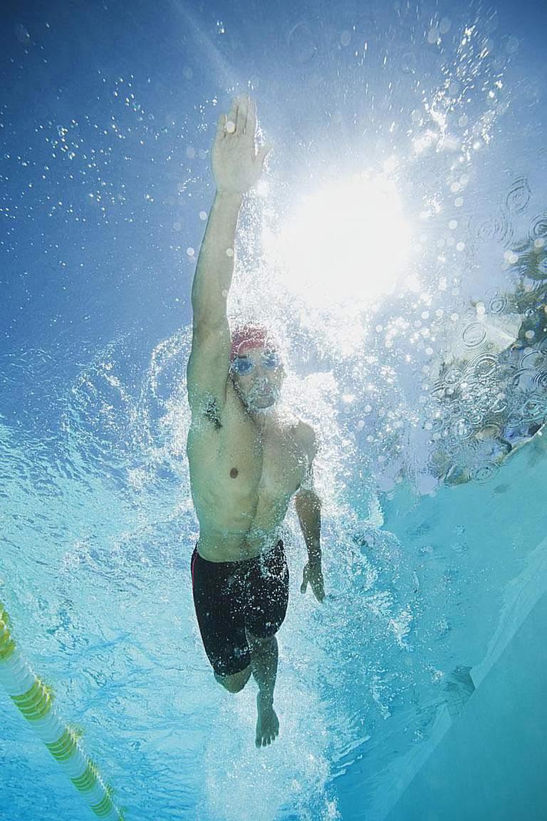 Mixed race man swimming in swimming pool