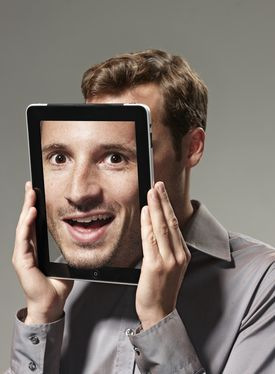 Man with digital tablet displaying a smiling face