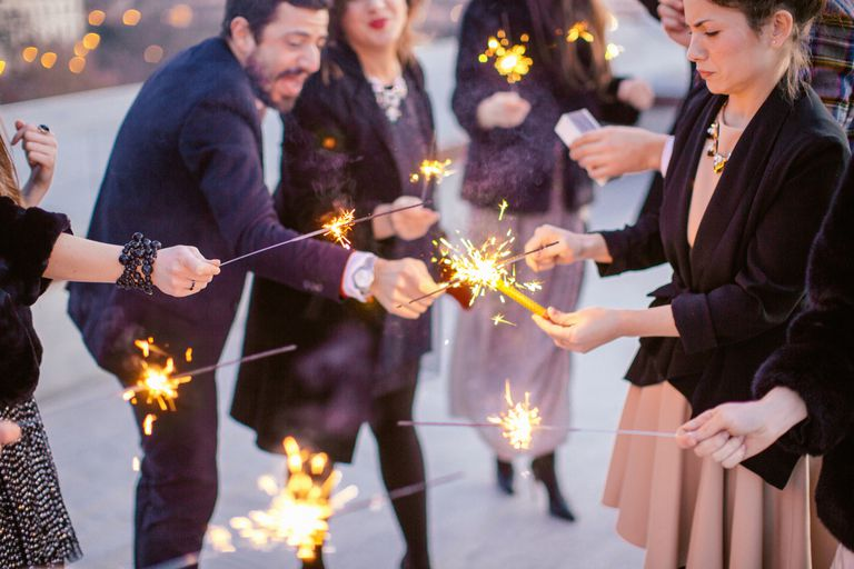 Group of friends waving sparklers, at party