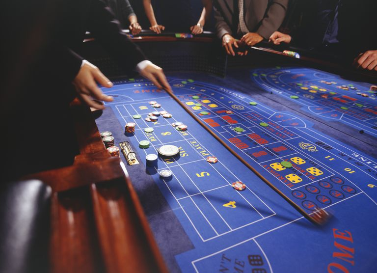 People playing craps in casino, croupier collecting chips