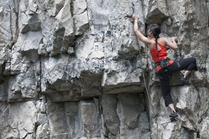 Climber scaling steep cliff face