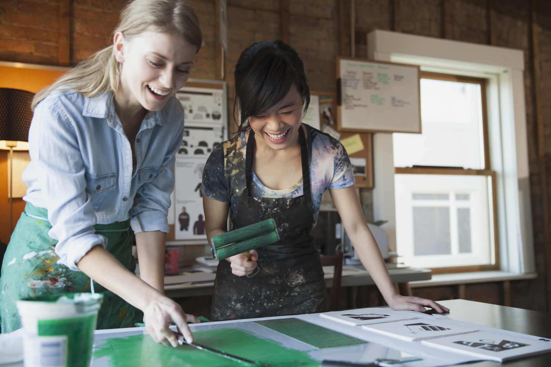 Happy female design professionals inking up etching plates for printmaking