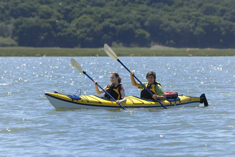 Tandem kayakers paddling in unison