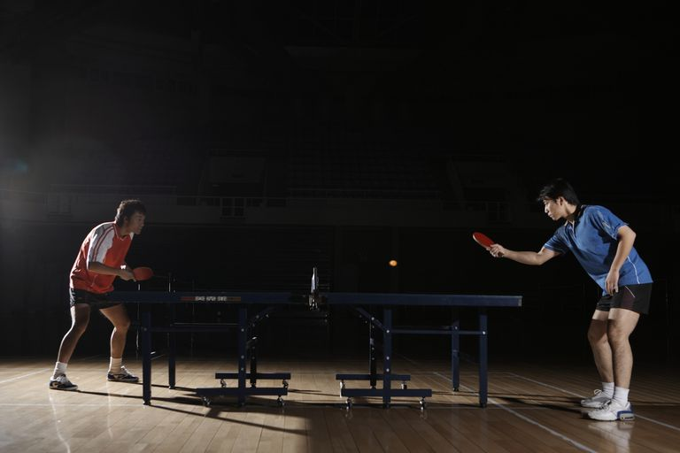 Two young men playing table tennis, side view