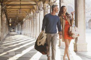 Smiling couple walking along corridor in Venice