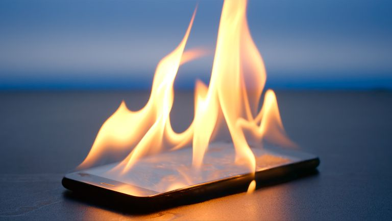 Smartphone is burning on a table on a blue background